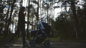 Movimento lento - la madre snella cammina con un passeggiatore nella foresta al sole video d archivio