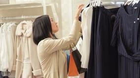 Movimento lento La ragazza castana attraente sceglie il vestito Vestiti castana dei buys della bella donna in deposito Signora gr archivi video