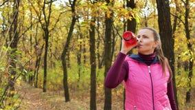 Movimento lento A menina bonita do esporte da aptidão no sportswear bebe a água ou a bebida isotonic de uma garrafa de água dos e filme