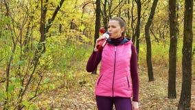 Movimento lento A menina bonita do esporte da aptidão no sportswear bebe a água ou a bebida isotonic de uma garrafa de água dos e video estoque