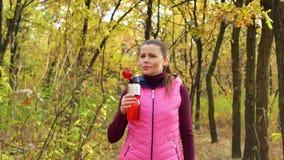 Movimento lento A menina bonita do esporte da aptidão no sportswear bebe a água ou a bebida isotonic de uma garrafa de água dos e vídeos de arquivo