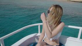 Movimento lento Menina bonita em um biquini, em um iate Poses no fundo do oceano O cabelo torna-se no vento video estoque
