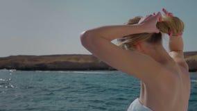 Movimento lento Menina loura bonita no biquini, em um iate Recolhe o cabelo em um bolo Poses no fundo do mar filme