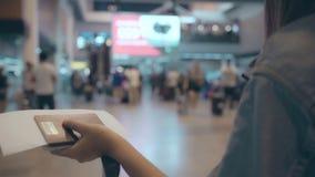 Movimento lento - mulher asiática feliz que usa o trole ou o carro com muito a bagagem que anda no salão terminal ao ir ao voo de filme