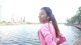 Movimento lento - a mulher bonita asiática em equipamentos da aptidão está usando um smartwatch para escuta a música, falando no  vídeos de arquivo