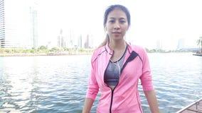 Movimento lento - a mulher bonita asiática em equipamentos da aptidão está usando um smartwatch para escuta a música, falando no  filme