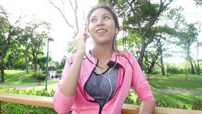 Movimento lento - a mulher bonita asiática em equipamentos da aptidão está usando um smartwatch para escuta a música, falando no  video estoque