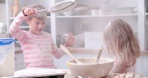Movimento lento sparato dei bambini che hanno divertimento sudicio in cucina video d archivio