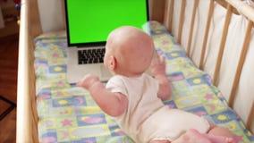 Movimento lento superior do bebê bonito que crowling ao portátil com tela do chromakey vídeos de arquivo