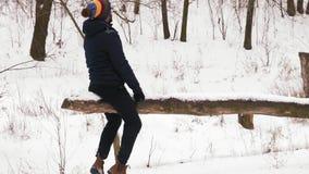 Movimento lento, tipo indiano e bello giro della donna su un'oscillazione nella foresta di inverno archivi video