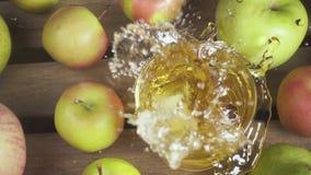 Movimento lento um o vidro do suco em uma tabela entre a opinião superior das maçãs vídeos de arquivo