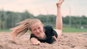 Movimento lento: uma jovem mulher que salta na queda bate a bola na areia O jogador de voleibol faz uma equipe e joga vídeos de arquivo