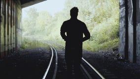Movimento lento Uomo che corre in avanti sulla ferrovia Vista posteriore Colpo astratto della siluetta Concetto di quanto segue i stock footage