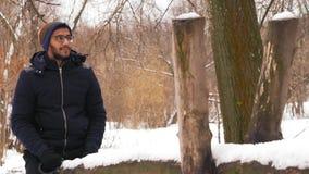Movimento lento, uomo indiano nei giri di vetro su un'oscillazione di legno nell'inverno nella foresta stock footage