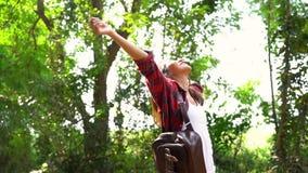 Movimento lento - viajante asiático novo feliz da mulher com trouxa que anda na floresta video estoque