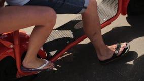 Movimento maduro do homem e da mulher no 'trotinette' assentado automático vermelho no dia de verão filme