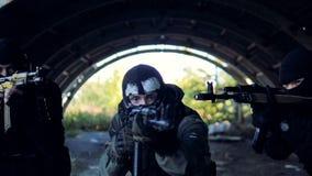 Movimento mascarado de três homens com os rifles que apontam em todos os sentidos
