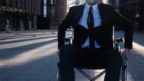 Movimento novo do homem de negócios na cadeira de rodas no centro de negócio próximo exterior da câmera filme