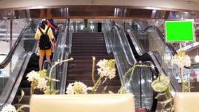 Movimento rápido dos povos que tomam a escada rolante com placa de tela verde dentro do shopping filme