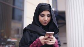 Movimento rotondo della macchina fotografica: Hijab d'uso della giovane donna attraente che sta nella via, scrivente un messaggio video d archivio