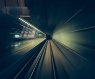 Movimento veloce di un treno tramite i tunnel ferroviari catturati dall'interno della cabina di un treno POV immagine stock