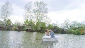 Movimentos da câmera longe dos recém-casados de riso felizes que que sentam-se em um barco branco video estoque