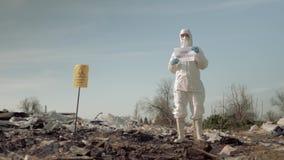 Movimiento ambiental, muchacha en máscara y cartel de la tenencia del traje con lema de la contaminación de la parada en la desca almacen de video