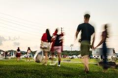 Movimiento borroso de la gente que camina a través de un parque a un concierto al aire libre imagen de archivo