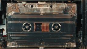 Movimiento de carretes con la cinta magnética en un casete audio viejo almacen de metraje de vídeo