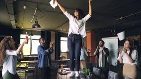 Movimiento de Clow del baile alegre de la señora joven en la tabla en las fiestas en la oficina con la pila de papel y de documen almacen de metraje de vídeo