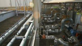 Movimiento de depósitos de aceite en la sol brillante al trabajador en los tubos almacen de video