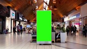 Movimiento de hacer compras de la gente y de la cartelera verde de la pantalla en el centro metrajes