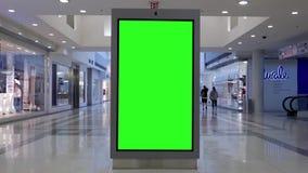 Movimiento de hacer compras de la gente y de la cartelera verde de la pantalla en el centro almacen de metraje de vídeo