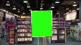 Movimiento de hacer compras de la gente y de la cartelera verde de la pantalla en el centro almacen de video