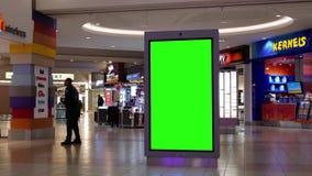 Movimiento de hacer compras de la gente y de la cartelera verde de la pantalla en el centro