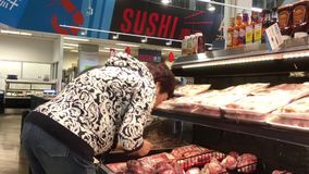 Movimiento de la carne de compra de la gente en la sección de la carne fresca metrajes
