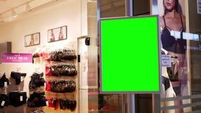 Movimiento de la cartelera verde para su anuncio al lado de vender la entrada de la tienda del sujetador