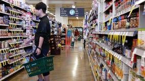 Movimiento de la comida de compra de la gente dentro de la tienda de comidas elegante del precio almacen de metraje de vídeo