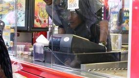 Movimiento de la comida de compra de la gente en el carnaval de las diversiones de la costa oeste almacen de metraje de vídeo