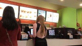 Movimiento de la comida de compra de la gente en el restaurante de los alimentos de preparación rápida de A&W metrajes