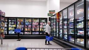Movimiento de la comida de la compra de la mujer dentro de la tienda de Walmart almacen de metraje de vídeo