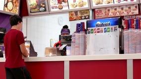 Movimiento de la comida de compra de la gente en el restaurante de KFC