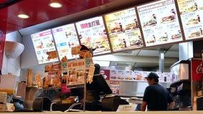 Movimiento de la comida que ordena de la gente en el contador de pago y envío dentro de reyes de la hamburguesa metrajes