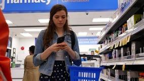 Movimiento de la comida sana de compra y de comprobar de la gente el teléfono celular en la sección de la farmacia
