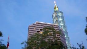 Movimiento de la conducción de automóviles por Taipei 101 en la tarde