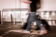 Movimiento de la falta de definición de los pasajeros que caminan en el aeropuerto Imagen de archivo libre de regalías