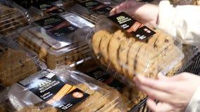 Movimiento de la galleta de compra de la gente dentro de la tienda de Walmart