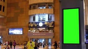 Movimiento de la gente busying a tomar el tren en la noche con el tablero verde del tráfico de la pantalla metrajes