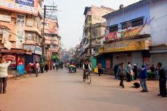 Movimiento de la gente con los ciclos en la calle india ocupada con los edificios viejos Imagenes de archivo