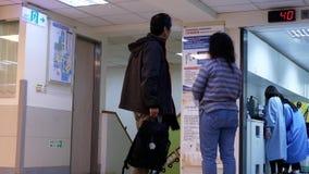 Movimiento de la gente que busca una estación de la recepción dentro del hospital almacen de metraje de vídeo